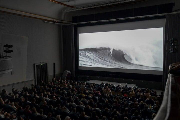 Vollbesetzter Kinosaal mit Surfermovie auf der Leinwand.